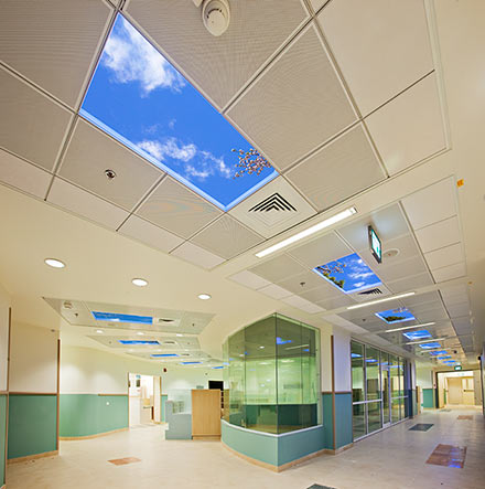 Corridors around the centrally located nursing stations feature dozens of virtual skylights providing valuable biophilic stimulation in the windowless interior.